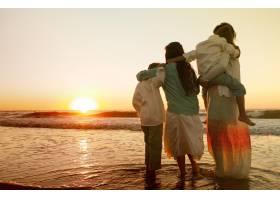 日落时分一家人站在大海环绕的海滩上拥抱_9932756