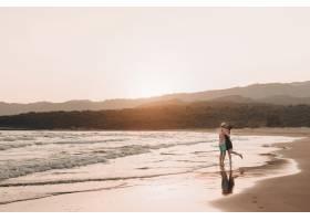 日落时分年轻的男女在海滩上接吻_3341313