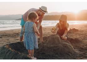 日落时分幸福的一家人在海滩上一起玩耍_3341304