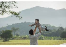 日落时分父子俩在公园里玩耍人们在球场_13012854