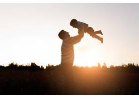 日落时分父子俩在公园里玩耍快乐的一家_3339135