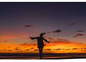 日落时海滩上的人们那个女孩在落日的背景_3064229