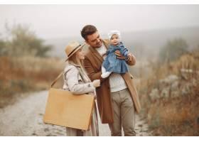 时髦的一家人走在秋天的田野上_8489287