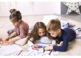 三个全神贯注的孩子在地板上玩耍在涂色书_7250343