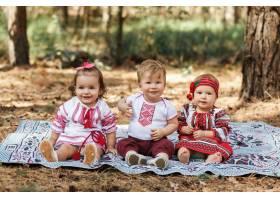 三个穿着传统乌克兰衬衫的孩子坐在春天森林_3337084