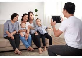 三位亚洲女士带着年幼的男孩和婴儿坐在沙发_5577336