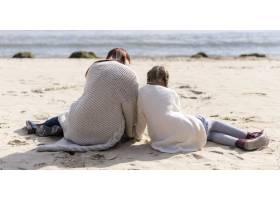 全景拍摄坐在沙滩上的母亲和孩子_11105705