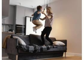 全景拍摄母亲和孩子在沙发上跳_13436830
