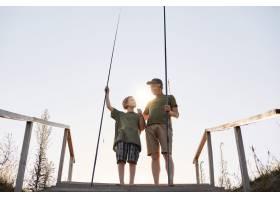 十几岁的男孩用钓竿学钓鱼爷爷教孙子钓鱼_9416286