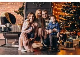 圣诞夜一大家子人在圣诞树旁送礼物_6426565