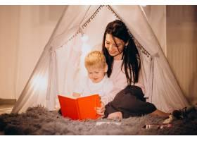 圣诞节母亲带着儿子坐在家里带着灯的舒适_3655270