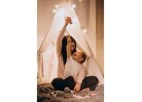 圣诞节母亲带着儿子坐在家里带着灯的舒适_3655272