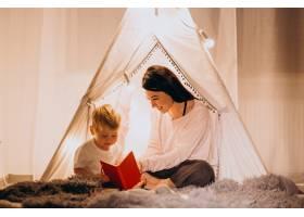 圣诞节母亲带着儿子坐在家里带着灯的舒适_3655273