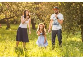 女儿和父母一起吹蒲公英_2586735