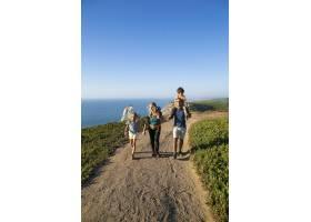 活跃的家庭夫妇和孩子沿着海边徒步旅行走_11293596