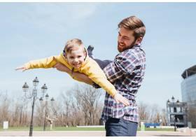 父亲和他的小儿子一起在公园里玩耍_7927356