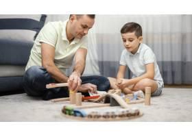 父亲和孩子在卧室里玩玩具_12396521