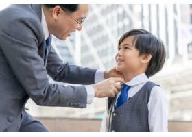 父亲在商业区市区为他的儿子做了西装的领子_11872261