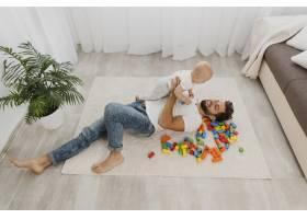 父亲在家中抱着婴儿在地板上玩耍的高角度_11904640