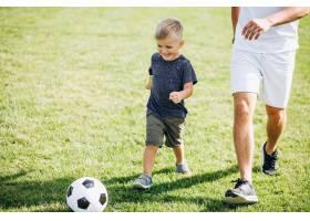 父亲带着儿子在球场上踢足球_5507445