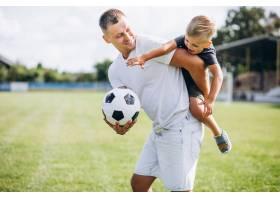 父亲带着儿子在球场上踢足球_5507446