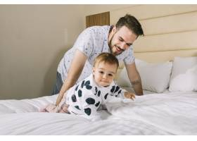 父亲带着躺在床上的婴儿_4795474