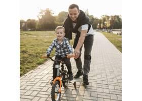 父亲帮他的儿子骑自行车_11176088