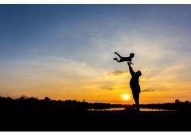 父亲把儿子扔向天空的剪影日落背景下的_1151012