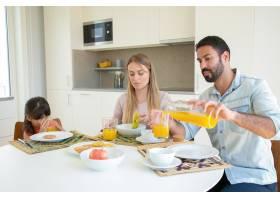 父母和孩子坐在餐桌前端着菜水果和饼干_9988588