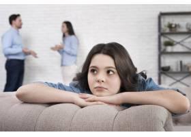 父母在背后争吵的悲伤女孩的肖像_8364982