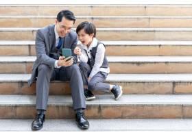 父子俩在商业区城市里一起玩智能手机_11872233
