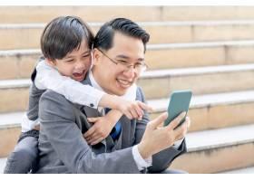 父子俩在商业区城市里一起玩智能手机_11872241