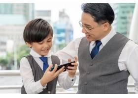 父子俩在商业区城市里一起玩智能手机_11872350