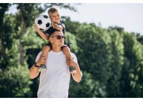 父子俩在海滩上踢足球_5507443