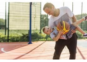 父子俩在篮球场上玩耍_11176291