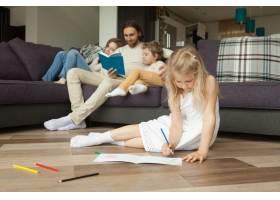 父母和儿子读书时女儿在地板上玩耍_3938139
