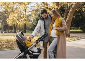 爸爸和妈妈带着孩子坐在户外的婴儿车里_11904687