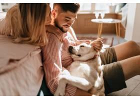 狗躺在主人的腿上穿粉色衬衣的男人和他心_12432329