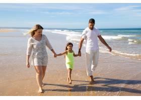 积极放松的家庭夫妇和小女孩走在海滩上潮湿_11076342