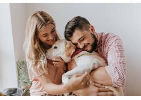 积极的夫妻和狗一起玩耍身着条纹衬衫的男_12432025