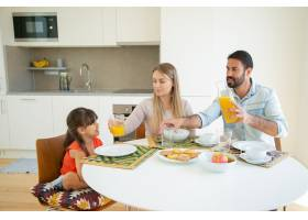 积极的父母和女儿坐在餐桌旁端着菜水果_9988599