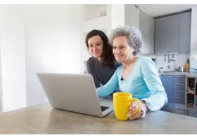 积极的高级女士在笔记本电脑上向女儿展示照_4167026