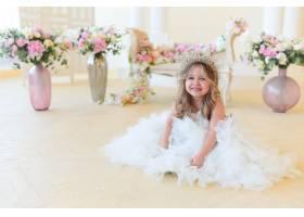 穿得像公主的小女孩坐在房间里的花丛中_2630565