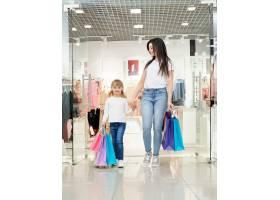 快乐的女人和孩子拿着商店里的购物袋_8792597