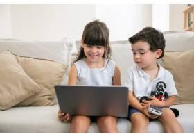 快乐的女孩和她的小弟弟坐在家里的沙发上_9988556