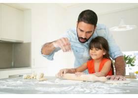 快乐的女孩和她的爸爸在厨房的桌子上揉面团_9988359
