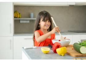 快乐的女孩用大木勺在碗里扔沙拉流行性感_9648987