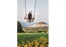 快乐的女性在背景模糊的草地上摇摆的垂直镜_8280948