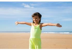 快乐的小女孩穿着夏装张开双臂站在海滩上_10579281
