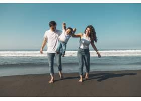 快乐的年轻家庭在阳光明媚的海滩上带着婴儿_4360489